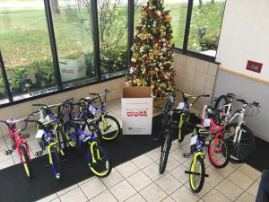 11 Bikes are posed in the corner of the main lobby for the DIA Toys for Tots Charity event supported by Trans-Overseas Corporation. In the center is a Toys for Tots donation box and behind it, a brightly lit and ornately decorated Christmas Tree.