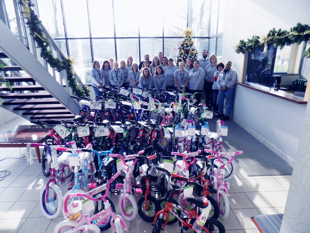 A group of Trans-Overseas employees stands in front of a  large plate glass windows and behind 43 children's bikes for the DIA Toys for Tots Charity event supported by Trans-Overseas Corporation. A Staircase ascends on the left side of the frame towards the camera while the bikes are arranged in 4 rows of 10 with 3 bikes in the immediate foreground. The receptionist's window is on the right of the frame.